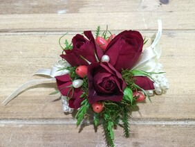 Red rose wrist corsage on pearl band
