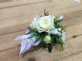 White wrist corsage on pearl band